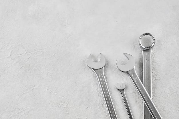 Quattro strumenti della chiave inglese su priorità bassa concreta di lerciume. vista dall'alto, copia spazio