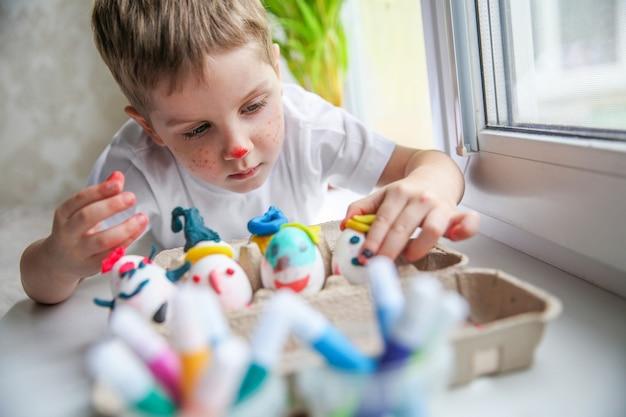 Un bambino di quattro anni con la faccia dipinta sdraiato sul davanzale della finestra mette le uova decorate per la pasqua in una scatola artigianale