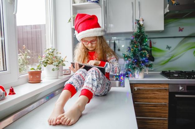 Una bambina di quattro anni con un cappello da babbo natale e occhiali scrive una lettera sul taccuino a babbo natale mentre è seduta sul tavolo della cucina