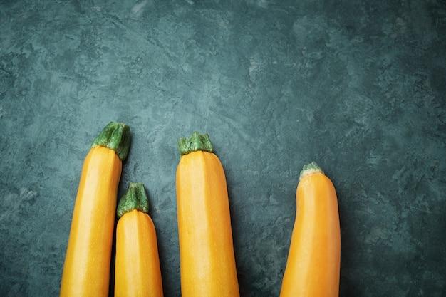 Quattro zucchine gialle sul tavolo della cucina. zucchine intere crude