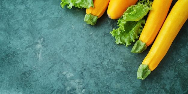 Quattro zucchine e lattughe gialle sul tavolo da cucina. zucchine intere crude