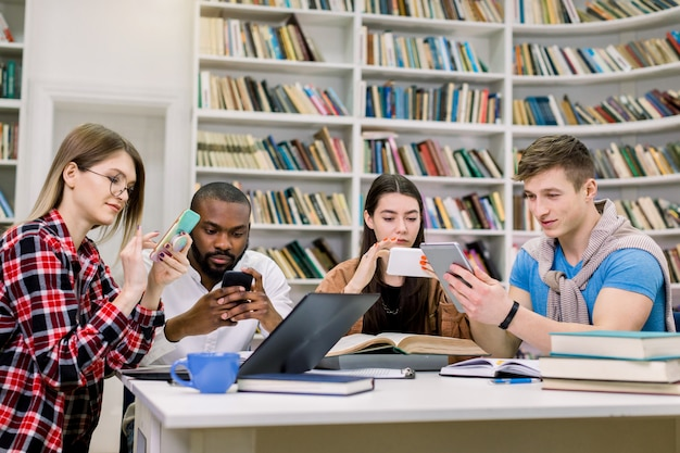 Quattro giovani amici studenti, ragazzi e ragazze di razza mista, che si stanno preparando per gli esami e cercano le informazioni necessarie sui loro smartphone