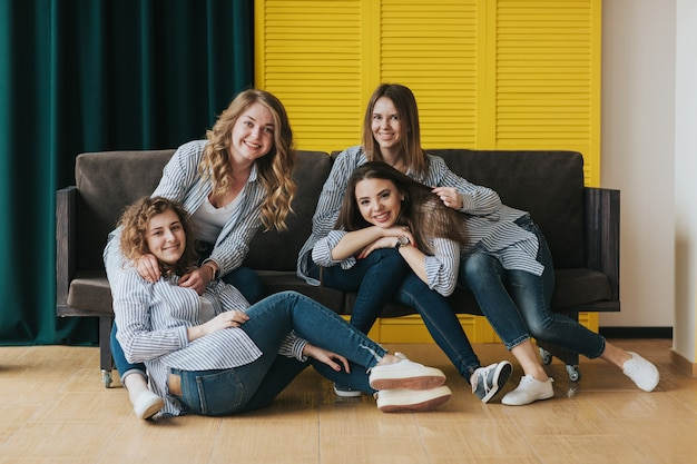 Quattro ragazze in camicie a righe, jeans e scarpe da ginnastica in posa sul divano