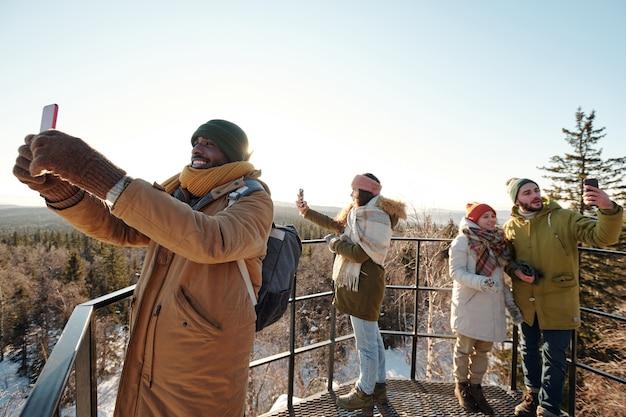 Quattro giovani amici interculturali che scattano foto di un bellissimo paesaggio