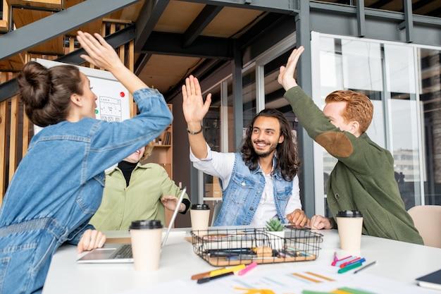 Quattro giovani colleghi gioiosi e di successo che si danno il cinque dopo aver discusso del nuovo progetto creativo durante la riunione di lavoro
