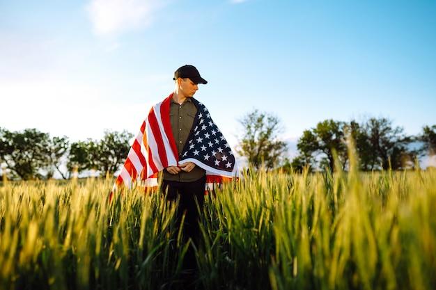 Quattro luglio. uomo patriottico con la bandiera americana nazionale nel campo. giovane uomo che sventola con orgoglio una bandiera americana. giorno dell'indipendenza.