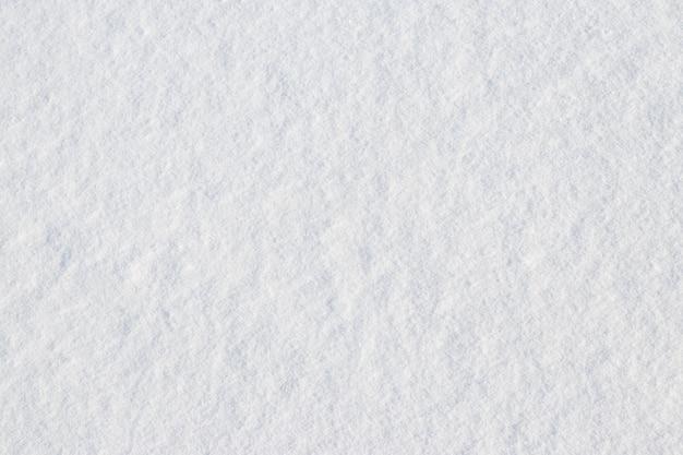 Texture di neve frazionata su una superficie piana, sfondo invernale