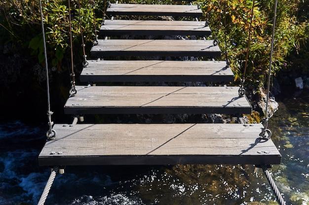 Frammento della costruzione di un ponte pedonale sospeso su un fiume poco profondo