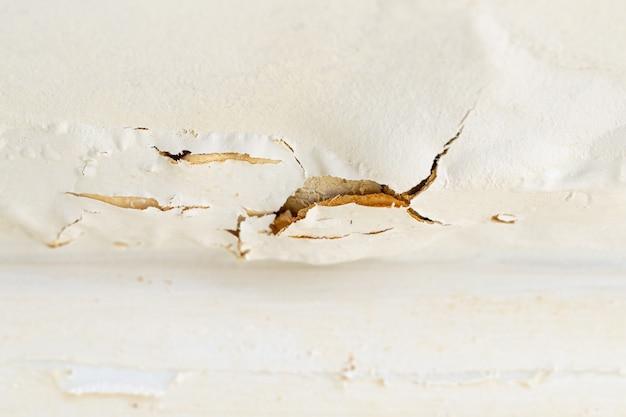 Frammento di intonaco screpolato sul soffitto dopo una perdita d'acqua dal piano superiore di un appartamento