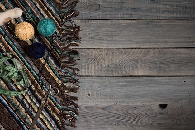 Frammento di tessuto a maglia fatto a mano, ferri da maglia e gomitoli di filato su lavagne bianche dipinte