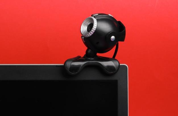 Frammento di un monitor con una webcam su colore rosso.