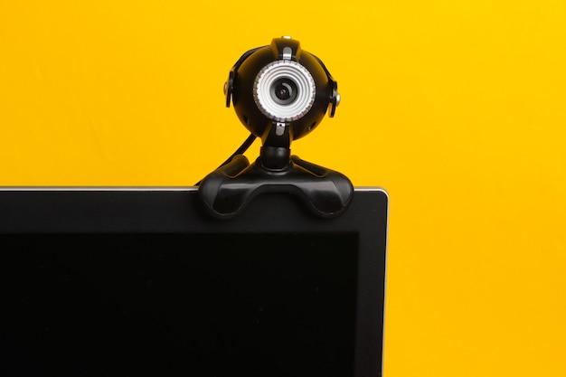 Frammento di un monitor con una webcam su uno sfondo giallo.