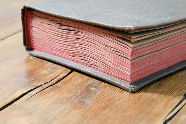 Frammento di vecchio libro che pone sulla superficie di legno stagionata