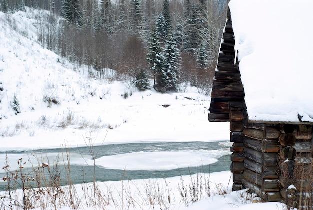 Frammento di una vecchia capanna di caccia di tronchi sulla sponda del fiume in un paesaggio invernale