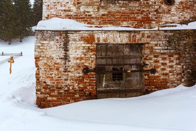 Frammento di una vecchia chiesa del villaggio con una porta chiusa a chiave su un sagrato invernale