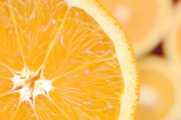 Frammento della fetta di frutta arancione sullo sfondo di molte fette d'arancia sfocate