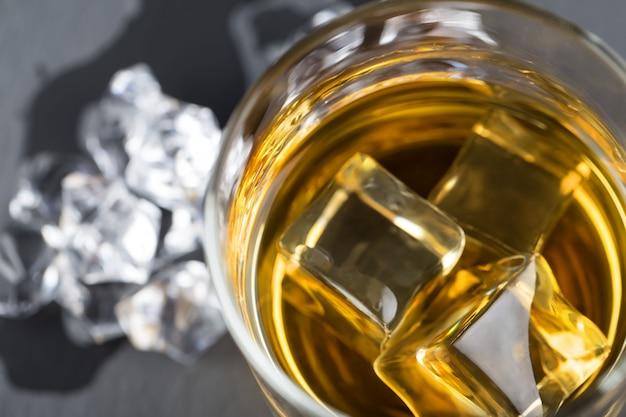 Un frammento di bicchiere rotondo di whisky con ghiaccio