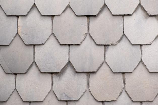 Un frammento di un muro fatto di piastrelle di pietra grigia di una vecchia casa europea. uso ideale per sfondi e trame.