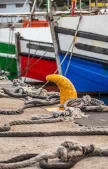 Frammenti di prua di pescherecci legati con funi al molo.