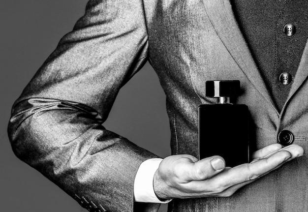 Odore di fragranza. profumi da uomo. bottiglia di colonia alla moda. uomo in abito formale, bottiglia di profumo, primo piano. bianco e nero.