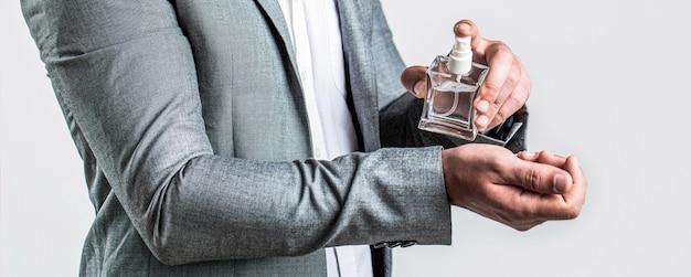 Odore di fragranza. profumi da uomo. bottiglia di colonia alla moda. uomo che regge una bottiglia di profumo