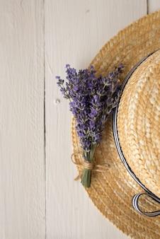 Un fragrante bouquet di lavanda giace su un cappello di paglia. vista dall'alto
