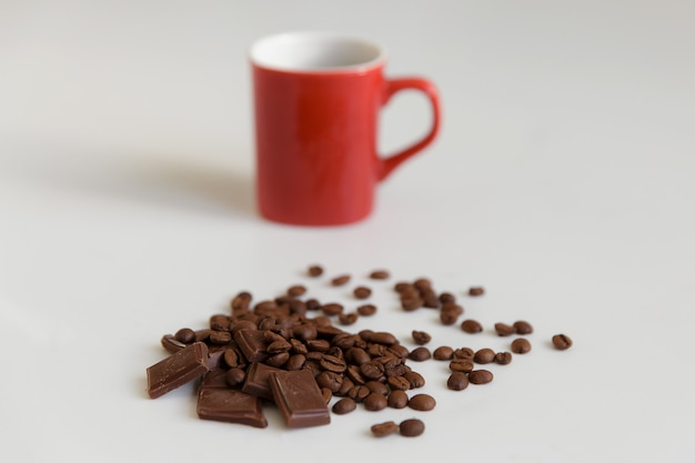 Caffè fragrante in combinazione con cioccolato delicato e tazza rossa.