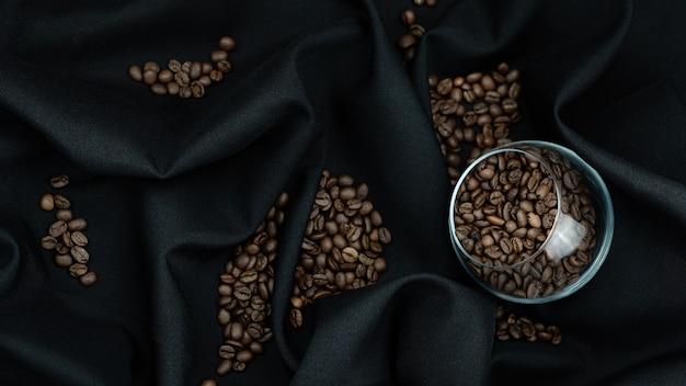 Profumato, caffè in grani in un bellissimo contenitore trasparente su fondo nero