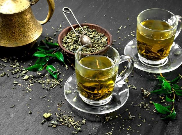 Tè verde profumato in tazze di vetro sulla lavagna nera