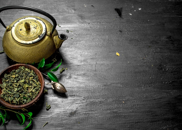 Tè verde profumato con foglie sulla lavagna nera