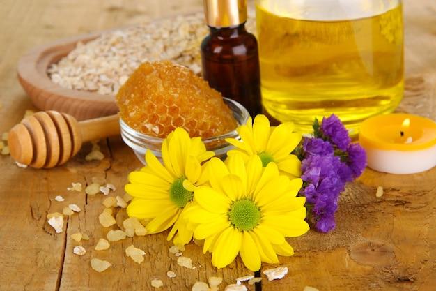 Spa di miele profumato con oli e miele sul primo piano del tavolo in legno