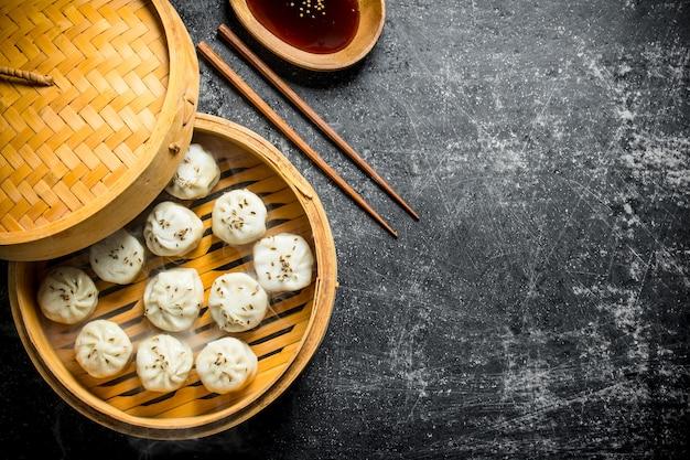Gnocchi di manta profumati in una vaporiera di bambù con salsa di soia in un piatto. su fondo rustico