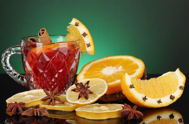 Vin brulè profumato in vetro con spezie e arance intorno sulla superficie verde