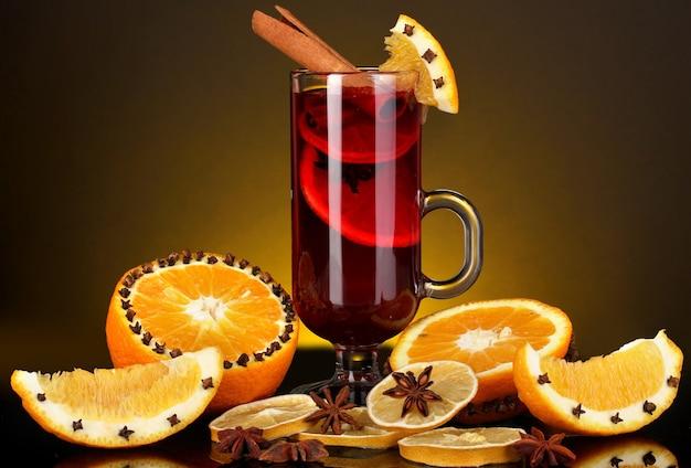 Vin brulè profumato in vetro con spezie e arance intorno sulla superficie gialla