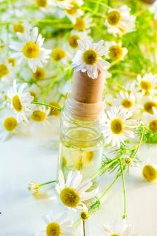 Olio profumato di fiori di camomilla in bottiglia di vetro