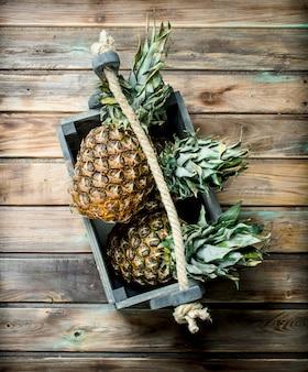 Ananas profumati nella confezione. sulla tavola di legno