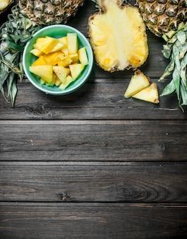 Fragranti fette di ananas maturo in una ciotola. sulla tavola di legno