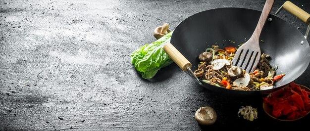 Tagliatelle di soba fragranti in una padella wok. sulla tavola rustica nera