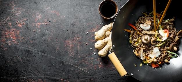 Fragranti tagliatelle di soba in padella wok con funghi e verdure fresche. sul tavolo rustico scuro