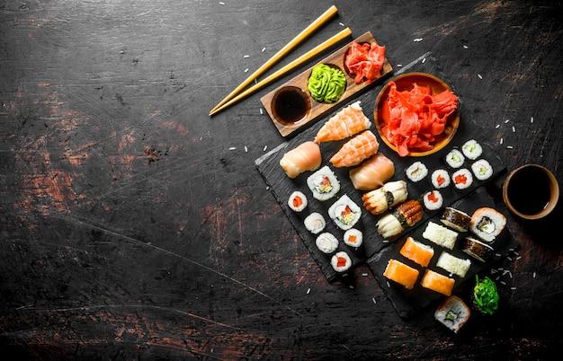 Involtini di sushi profumati con salmone, gamberetti e verdure. su fondo rustico scuro