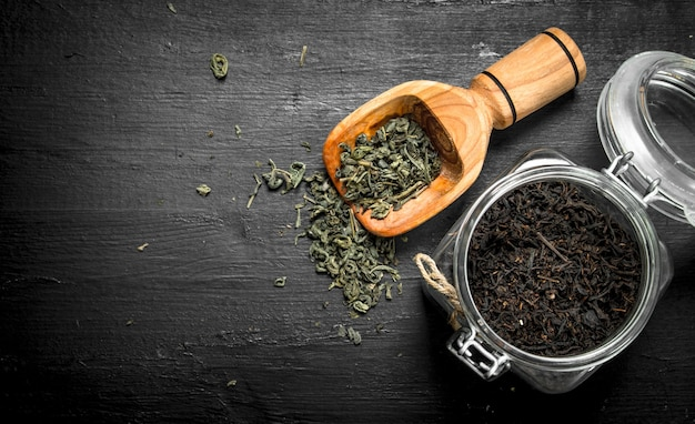 Tè profumato in barattolo di vetro. sulla lavagna nera.
