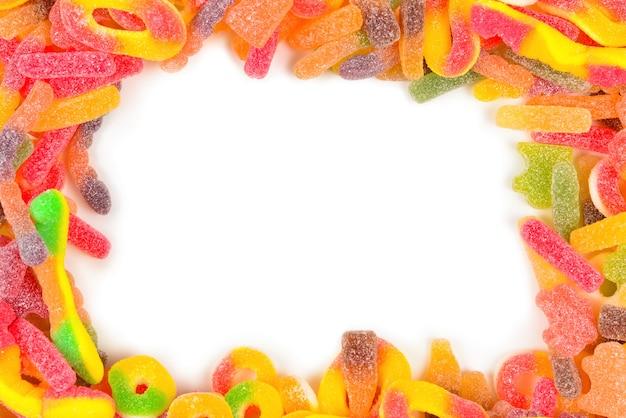 Cornice di caramelle gommose assortite isolato su bianco. vista dall'alto. spazio per testo o design.