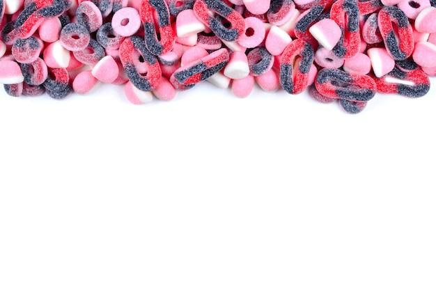 Cornice di caramelle gommose assortite isolate su bianco. vista dall'alto. spazio per testo o design.