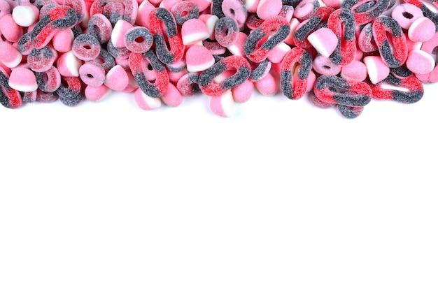 Cornice di caramelle gommose assortite isolate su bianco vista dall'alto