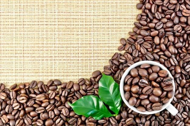 Una cornice di chicchi di caffè nero con foglie verdi e una tazza su un tessuto a trama grossa gialla