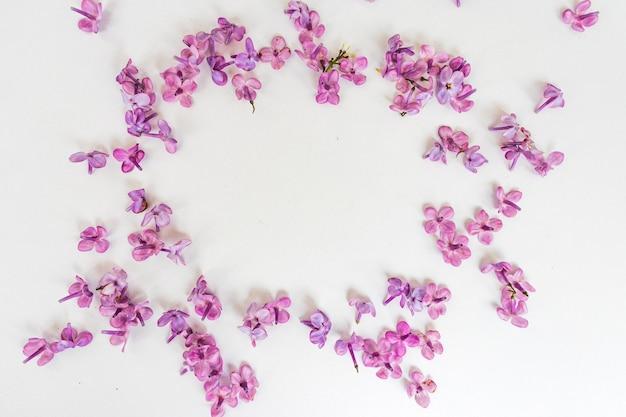 Cornice di rami e fiori di lillà su sfondo rosa. vuoto per biglietti per la primavera, pasqua, festa della mamma, festa della donna, san valentino. vista dall'alto, copia spazio