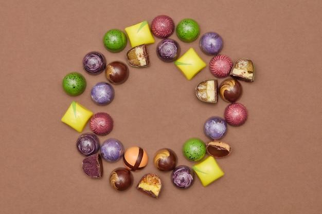 Cornice di cioccolatini su uno sfondo marrone.