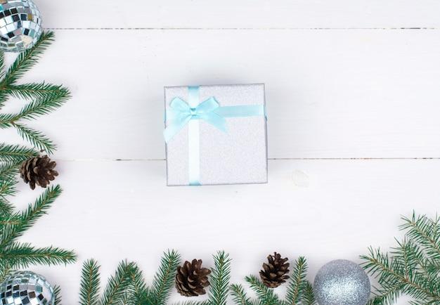 Cornice di decorazioni natalizie su sfondo bianco, rami di alberi, coni, regali flatlay, copyspace