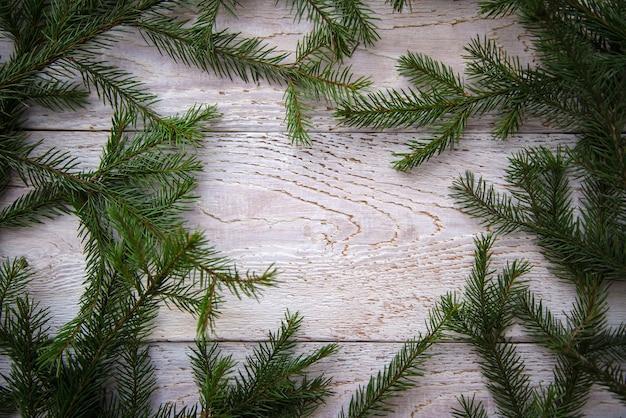 Cornice di rami di albero di natale su uno sfondo di legno