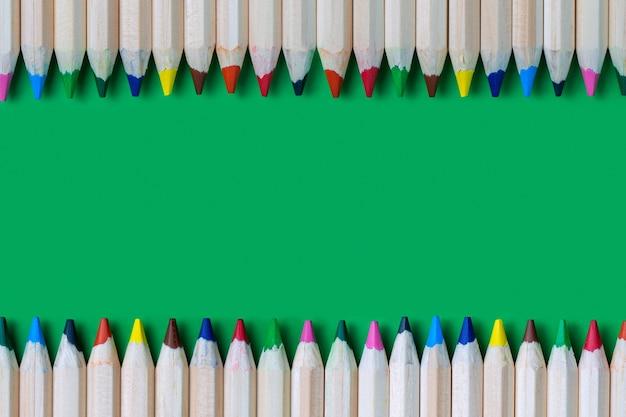 Cornice di matite colorate su una superficie verde